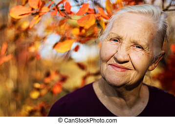 Autumn elderly woman - Portrait of the smiling elderly woman...