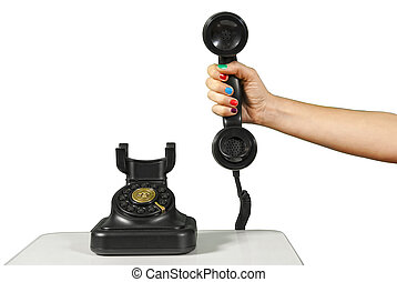 Hand holding an old black vintage telephone - A hand holding...
