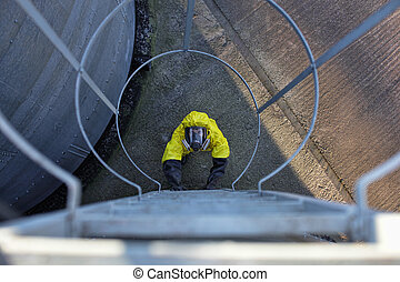 worker going up a metal ladder - aerial view of specialist...
