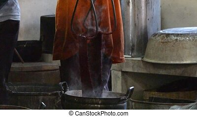 silk dyeing - silks being dye into red colors