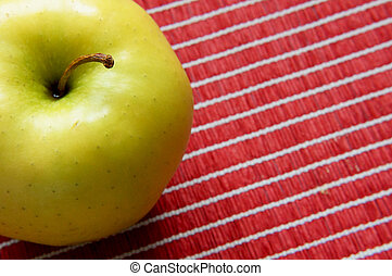 golden apple on a red tablecloth - Close-up view of a golden...