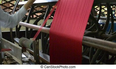 silk factory - winding of dyed red silk into a drum