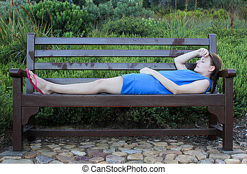 Woman lying on a Bench very tired