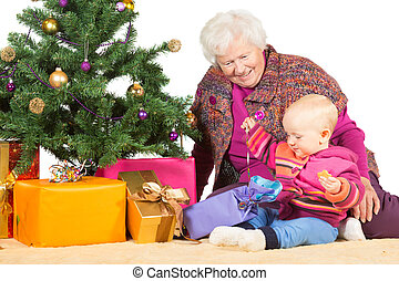Gran and baby unwrapping Christmas gifts - Cheerful elderly...