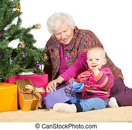 Grandmother babysitting young baby sitting together on the...