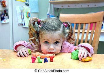 Play with Me - Small girl sits at a table with playing dough...