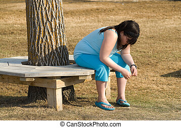 Sad Girl - Young girl sitting on a bench looking depressed