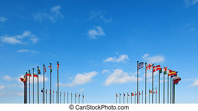 Flags of different countries on a flagpole against a blue...