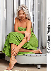 Beautiful girl in the solarium - Girl sits in a vertical...