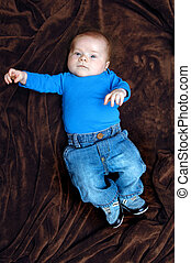 Baby Loves his Blue Jeans - Infant boy lays full length on a...