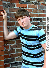 Alley Wall - Young man relaxes against an aging brick wall....