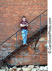 Alley Propped - Young man leans against an aging brick...