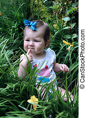 Decision Making - Little child sits in deep grass with a...