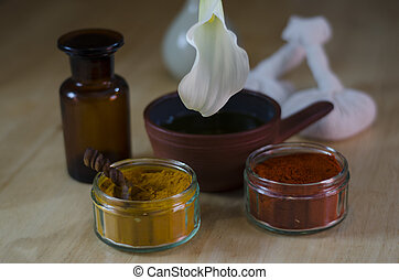An arrangement of turmeric and cayenne spices, oil bowl and...
