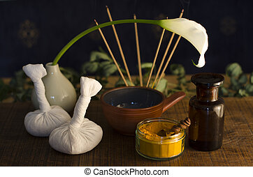 An arrangement of turmeric, spice, oil bowl and bottle, and...