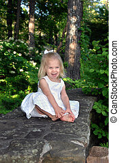 Angel laughs hilariously - Little girl sits on a stone fence...
