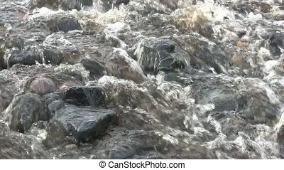 Close up of a stream flowing over stones on a beach
