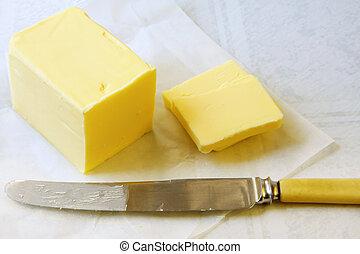 Butter - Block of golden butter, sliced with a bone-handled...