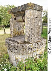 Wishing well - An Antique stone water well on village green...