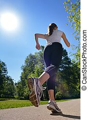 Young beautiful woman jogging at morning in park - Young...