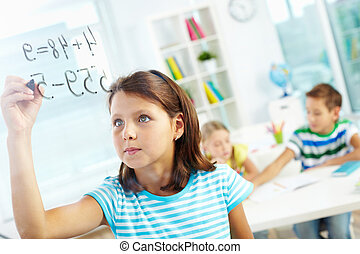 Schoolwork - Portrait of lovely girl doing sums on...