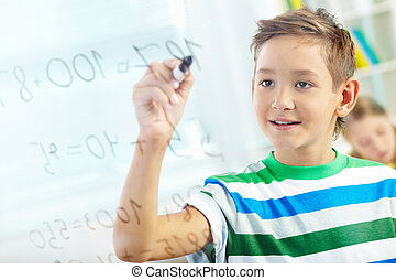 Mathematics - Portrait of handsome learner doing sums with...
