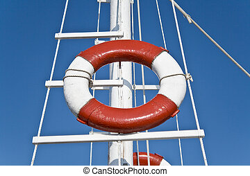 Life buoy and sailing mast over blue sky