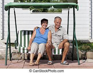 Senior loving couple have a rest in a swing chair