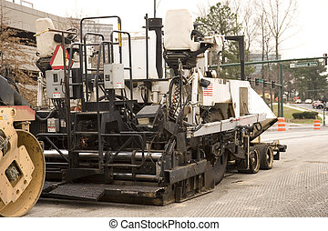 Asphalt Paving Machine - An asphalt paving machine on the...