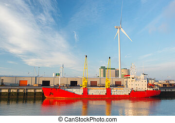 Cargo boat in harbor - Red loaded cargo boat and wind mill...