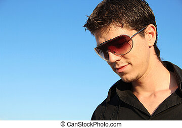 Fashion man portrait in sunglasses over blue sky