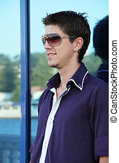 Fashion portrait of the young beautiful man in sunglasses
