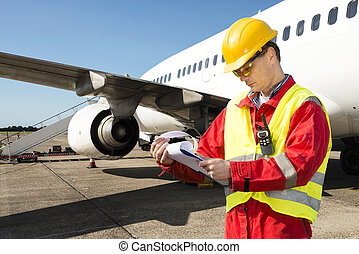 Aircraft engineer with a checklist of several pages on a...