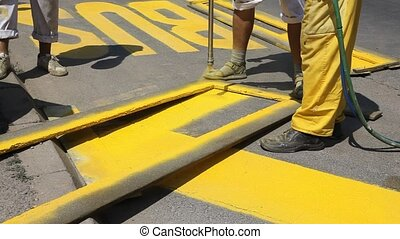 Roadworks -  Hand spraying of bus station sign at a street