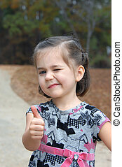 Thumbs Up - Little girl gives a thumbs up sign and winks She...
