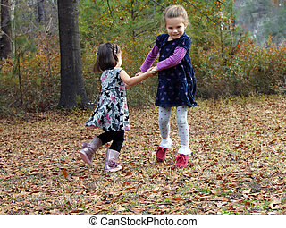 Autumn Games - Two little girls hold hands and swing in...