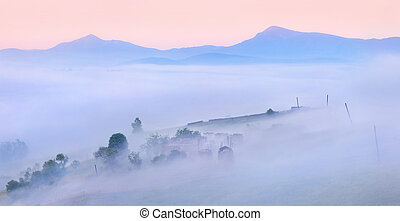 Silhouettes of the mountains and village in the morning mist...