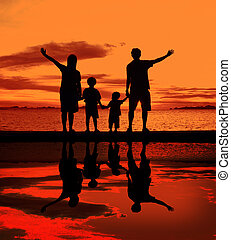 family - silhouette of family on the beach at dusk.