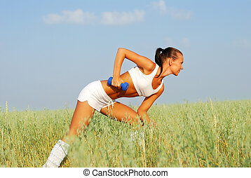 Woman Weight Training - Woman lifting dumbbell on wheat...