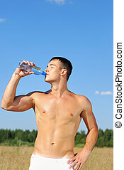 Young man drinking water after training