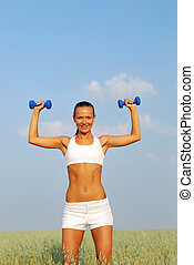 Woman lifting dumbbell on  wheat field