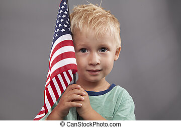 Young Boy Holds American Flag - A cute young boy holds an...