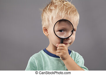 Cute Boy Holds Magnifying Glass