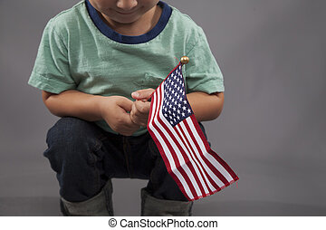 All American Boy - A little boy holds an American flag and...