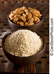 Almond Flour - Raw almond meal (flour) and almonds in wooden...