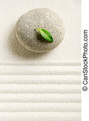 Zen Still Life - Stone on white raked sand with a green leaf...
