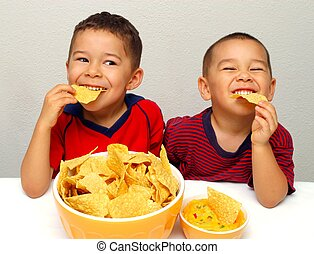 Kids eating chips having fun - Two brothers, aged 5 and 6...