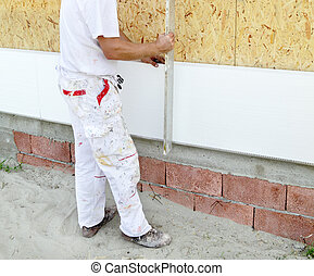 Insulation - Worker placing styrofoam sheet insulation using...