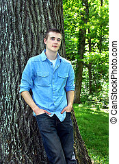 Blue Eyes and Blue Shirt - Young adult male leans against...