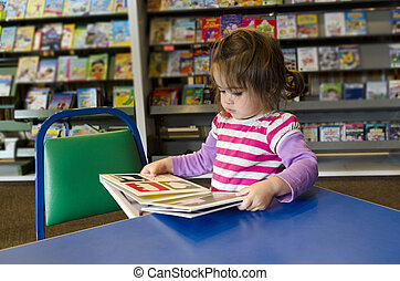 Child reads a book in library.